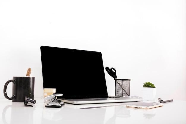 Laptop mit leerem bildschirm und mobiltelefon auf reflektierendem schreibtisch