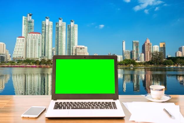 Laptop mit leerem grünem bildschirm auf holztischansicht draußen des bürohausstadtbilds