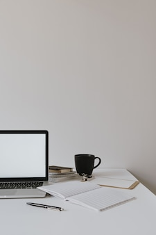 Laptop mit leerem kopierraum-modellbildschirm auf tisch mit kaffeetasse, blatt papier gegen weiße wand.