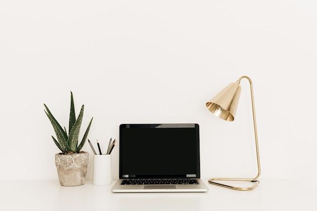 Laptop mit leerem kopierraumbildschirm auf weißem tisch mit goldener lampe und hauptpflanzenaloe vera