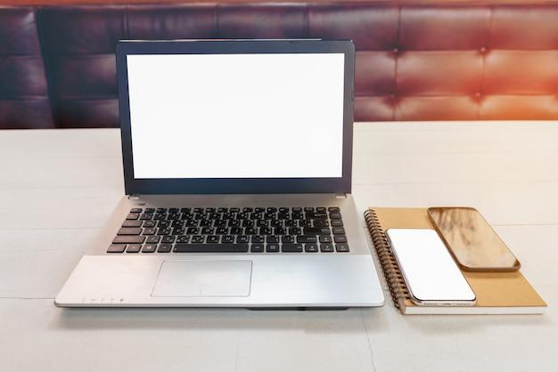 Laptop mit leerem notizbuch des weißen bildschirms und intelligentem telefon auf dem tisch im büroraum; notizbuch im coffeeshop.