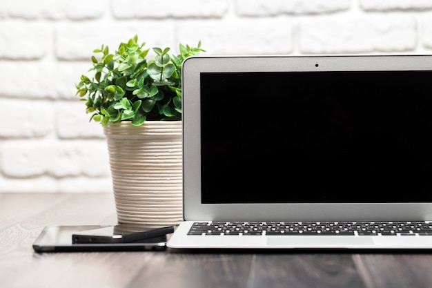 Laptop mit leerem schwarzem schirm auf einem holztisch gegen weiße backsteinmauer