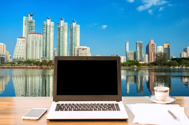 Laptop mit leerem schwarzem schirm auf holztischansicht draußen des bürohausstadtbilds