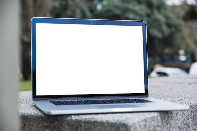 Laptop mit leerem weißem bildschirm an draußen