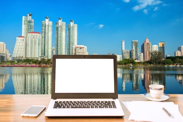 Laptop mit leerem weißem bildschirm auf holztischansicht draußen des bürohausstadtbilds
