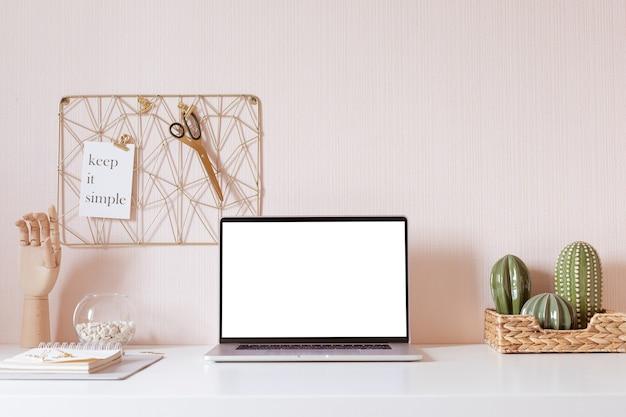 Laptop mit leerem weißem bildschirm auf schreibtischinnenraum. stilvolle goldarbeitsplatz-mockup-tabellenansicht.
