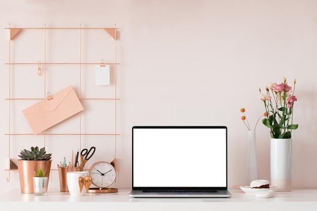 Laptop mit leerem weißem bildschirm auf schreibtischinnenraum. stilvolle roségoldene arbeitsplatzmodell-tabellenansicht.