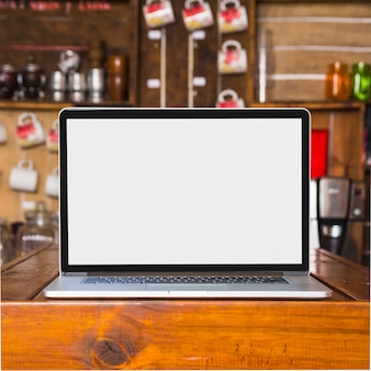 Laptop mit leerem weißem bildschirm auf tabelle im café