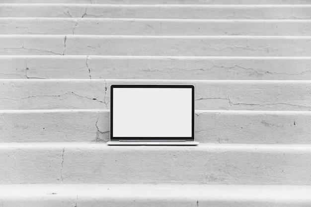Laptop mit leerem weißem bildschirm auf treppenhaus