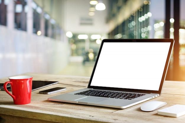 Laptop mit leerem weißem schirm auf tabelle im bürohintergrund