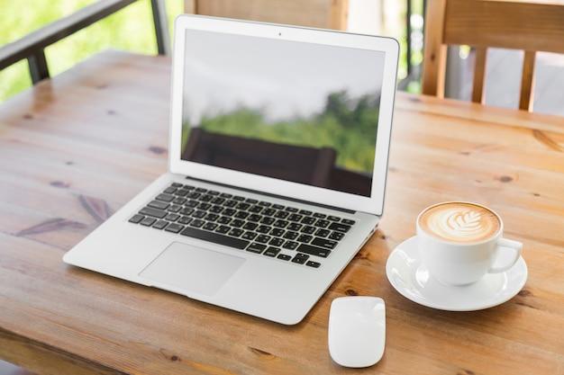 Laptop mit leeren bildschirm auf einem holztisch und eine tasse kaffee