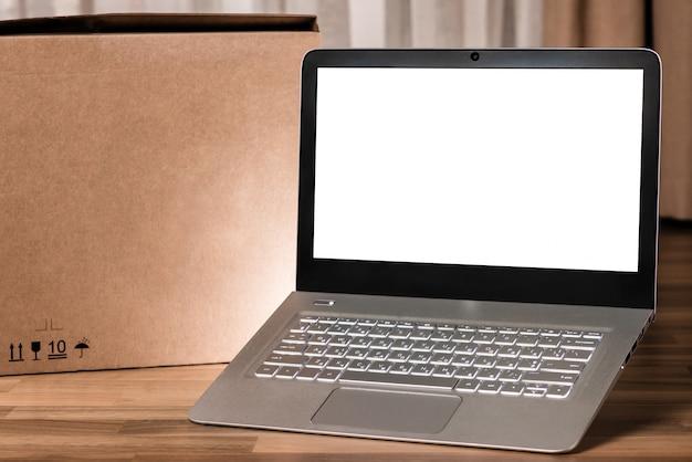 Laptop mit leeren bildschirm auf holztisch und unscharfen hintergrund