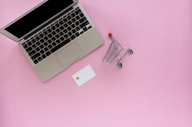 Laptop mit leerer kreditkarte und mini-einkaufswagen auf rosa hintergrund