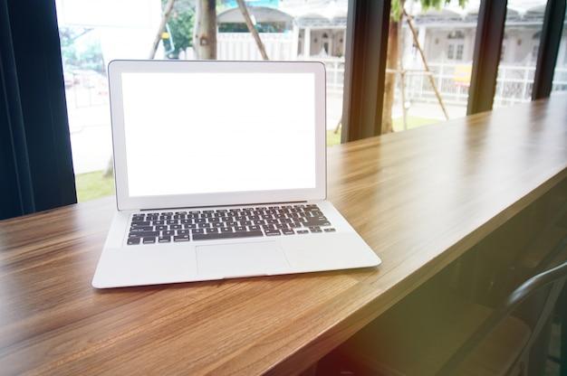 Laptop mit mock up leere bildschirm auf holztisch vor coffeeshop café platz für text. produktanzeige montagetechnik-konzept