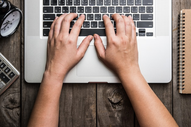 Laptop mit notizblock und uhr mit auf altem holztisch.