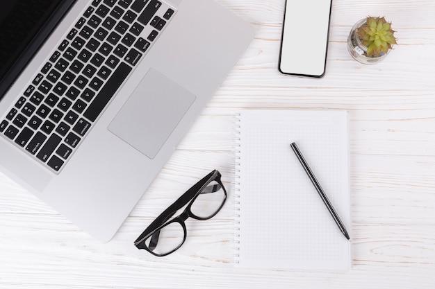 Laptop mit notizbuch und gläsern auf tabelle