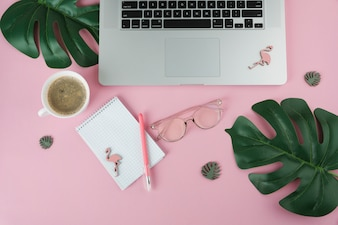Laptop mit Notizbuch und kleinen Flamingos auf Tabelle