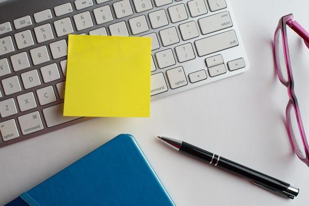 Laptop mit schwarzem stift, brille mit notizbuch