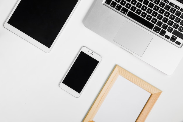 Laptop mit smartphone und leerem rahmen