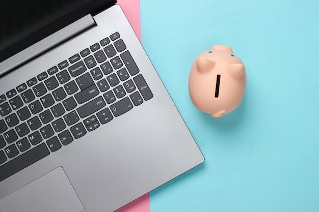 Laptop mit sparschwein auf rosa blauem pastell