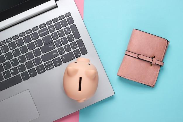 Laptop mit sparschwein, brieftasche auf rosa blauem pastell