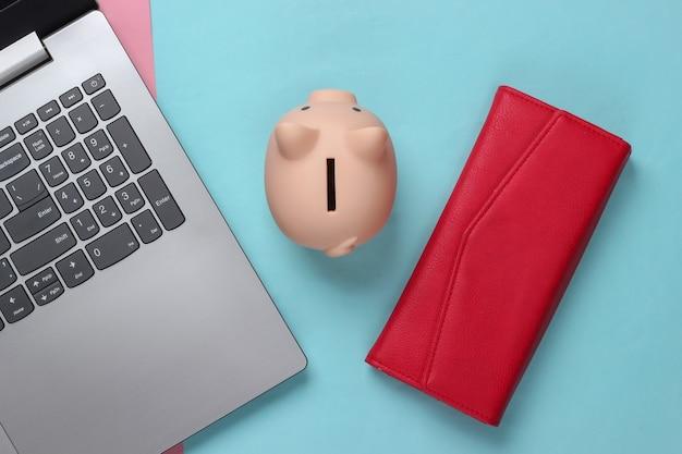 Laptop mit sparschwein, rote brieftasche auf rosa blauem pastell