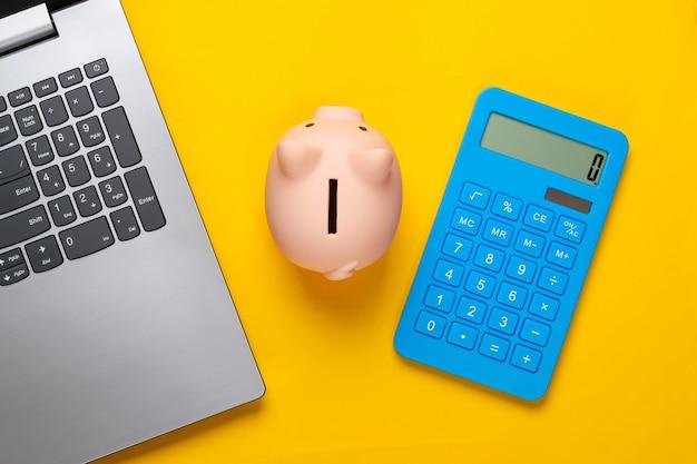 Laptop mit sparschwein, taschenrechner auf gelb
