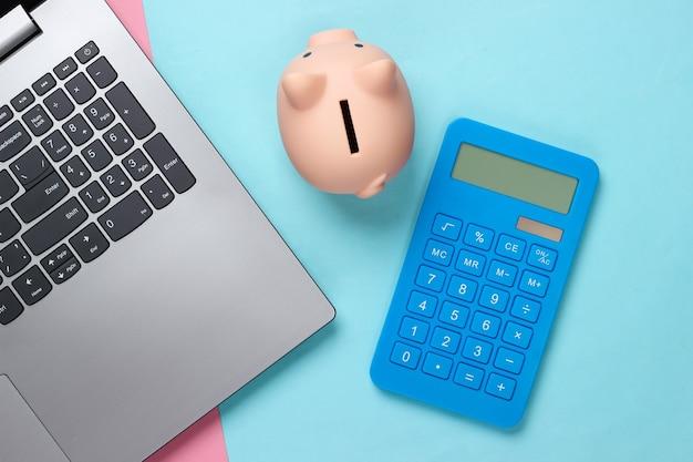 Laptop mit sparschwein, taschenrechner auf rosa blauem pastell