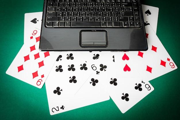 Laptop mit spielkarten auf grünem hintergrund.
