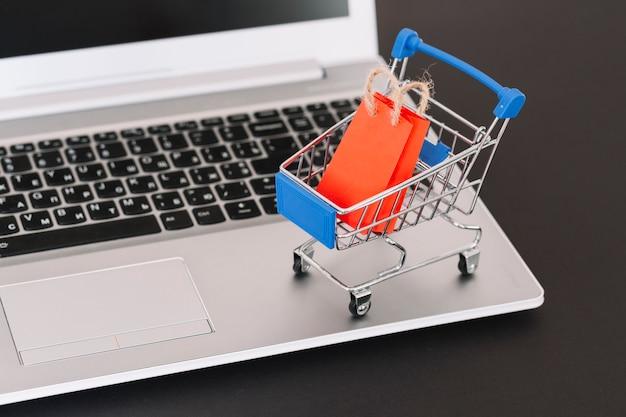 Laptop mit spielzeug supermarkt warenkorb und paket