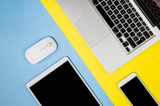Laptop mit tablette und smartphone auf tabelle