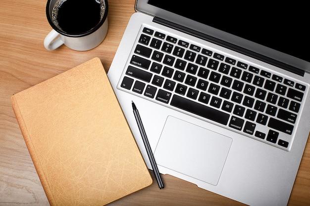 Laptop mit tasse kaffee und notizbuch auf holztischoberansicht