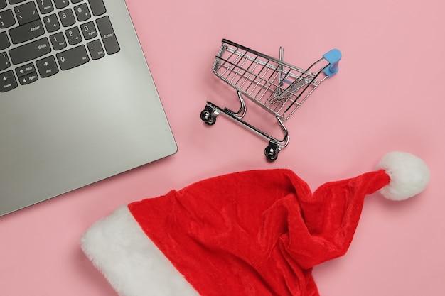 Laptop mit weihnachtsmütze, einkaufswagen auf rosa pastellhintergrund. weihnachtseinkauf. draufsicht