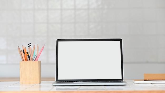 Laptop mit weißem leerem bildschirm, der auf modernen weißen keramikfliesentisch setzt.