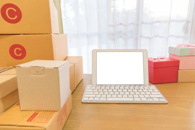 Laptop mit weißem leerem bildschirm und braunem paketkasten der verpackung.