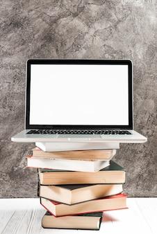 Laptop mit weißer Bildschirmanzeige auf dem Stapel Weinlesebüchern über der Tabelle gegen Betonmauer
