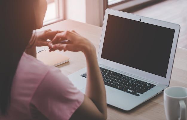 Laptop mock up mit asiatischen frau, die am computer zu hause mit leerem bildschirm arbeitet, für das arbeiten zu hause während der quarantänezeit.