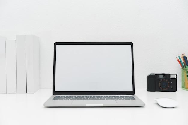 Laptop-modell mit leerem bildschirm auf weißem tisch mit maus. home interior oder büro hintergrund