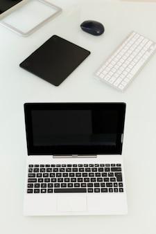 Laptop nahe grafischer tablette und tastatur