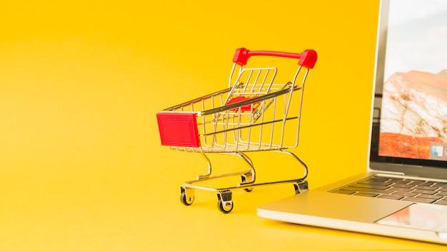 Laptop nahe supermarktwarenkorb mit rotem griff