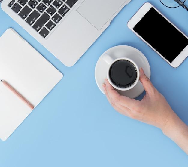 Laptop, notebook, smartphone und eine hand, die eine tasse kaffee auf hellblauem hintergrund hält