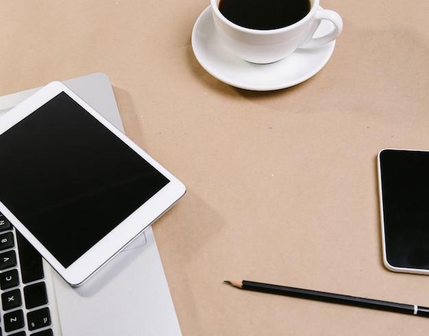 Laptop, notizblock, tablet und eine tasse espresso auf dem tisch