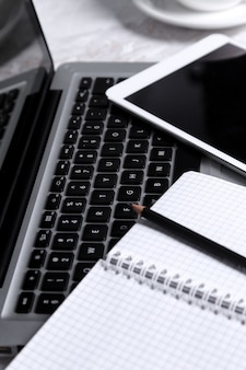 Laptop, notizblock und stift auf dem tisch