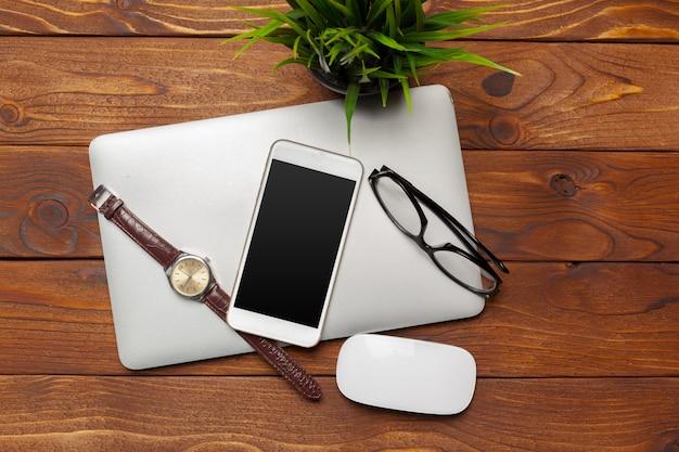 Laptop, notizbuch auf hölzernem schreibtisch der arbeit