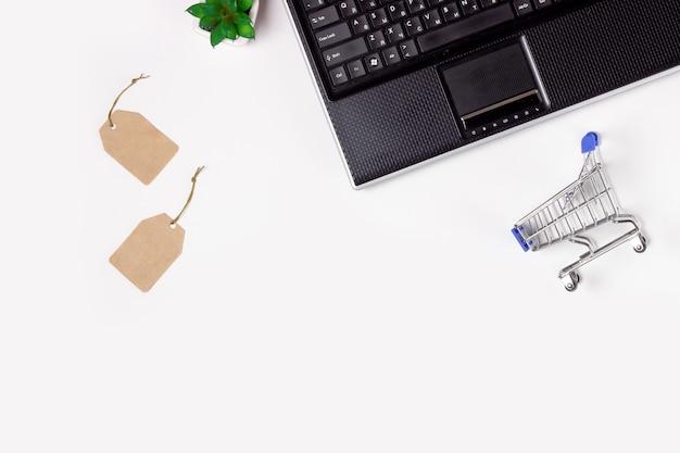 Laptop, notizbuch und einkaufswagen auf weißem hintergrund