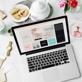Laptop-on-line-Einkaufs-Teekanne-Plätzchen-Blumen-Dekor-Konzept