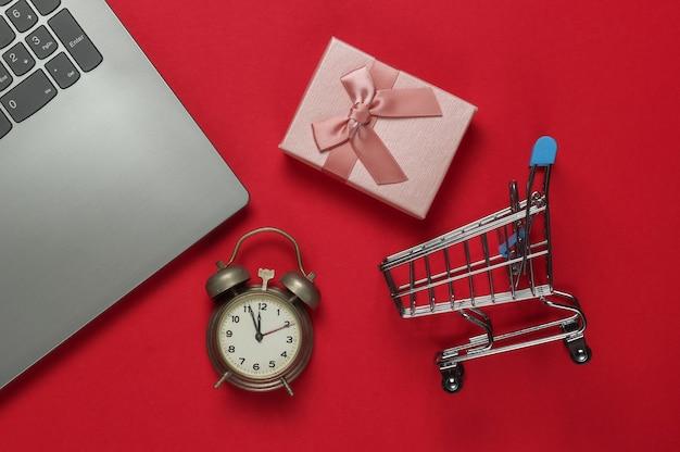 Laptop, retro wecker, einkaufswagen, geschenkboxen mit schleife auf rotem hintergrund. 11:55 uhr. neujahr, weihnachtskonzept. feiertage online-shopping. draufsicht