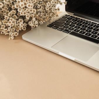 Laptop, schöner kamille-gänseblümchen-blumenstrauß auf pastellbeige tischhintergrund. arbeitsbereich für den home-office-schreibtisch.