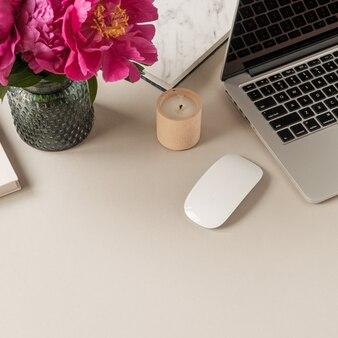 Laptop, schöner rosa pfingstrosen-tulpenblumenstrauß auf tisch. minimaler home-office-schreibtisch.