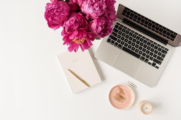 Laptop, schöner rosa pfingstrosen-tulpenblumenstrauß und notizbuch auf weißem tisch. flache lage, draufsicht